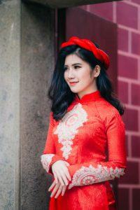 Traditional Vietnamese Ao Dai in red, worn by a beautiful Vietnamese woman